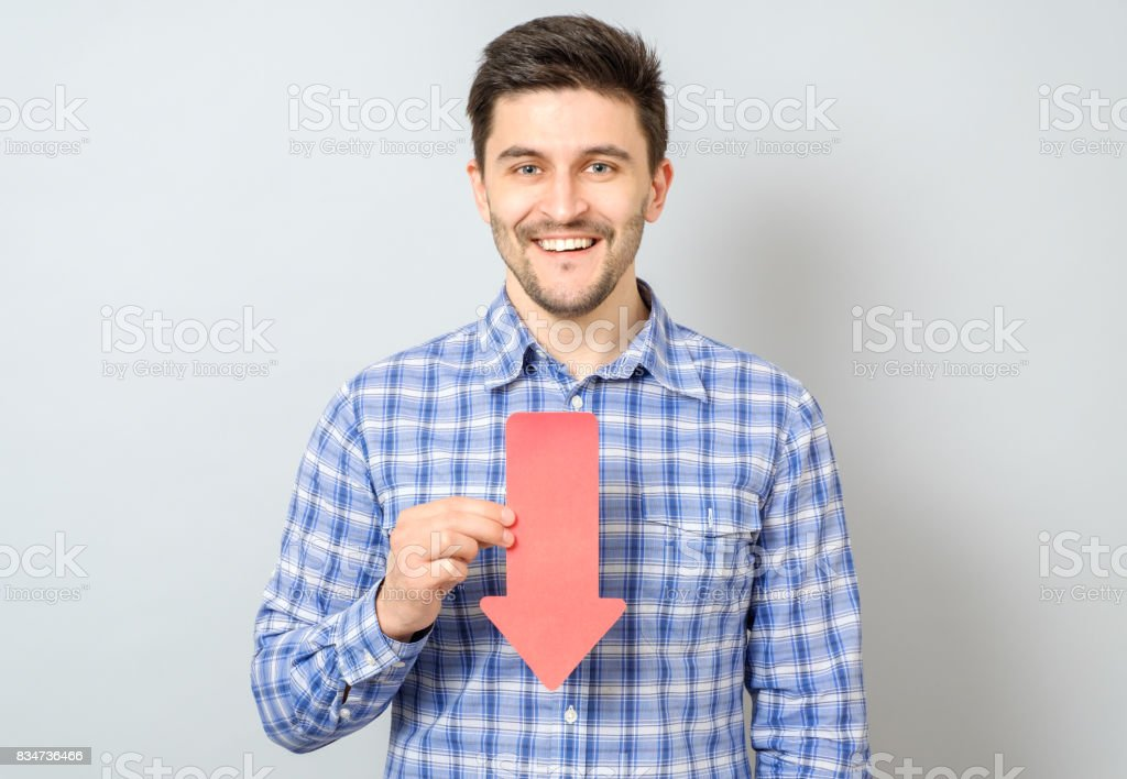 Man with arrow pointing to the down isolated on gray stock photo