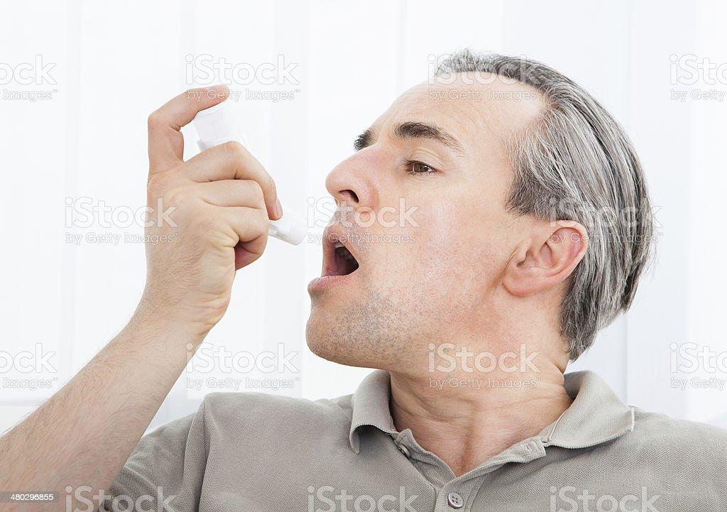 Man with asthma inhaler stock photo