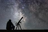 istock Man with astronomy  telescope looking at the stars. 642296174
