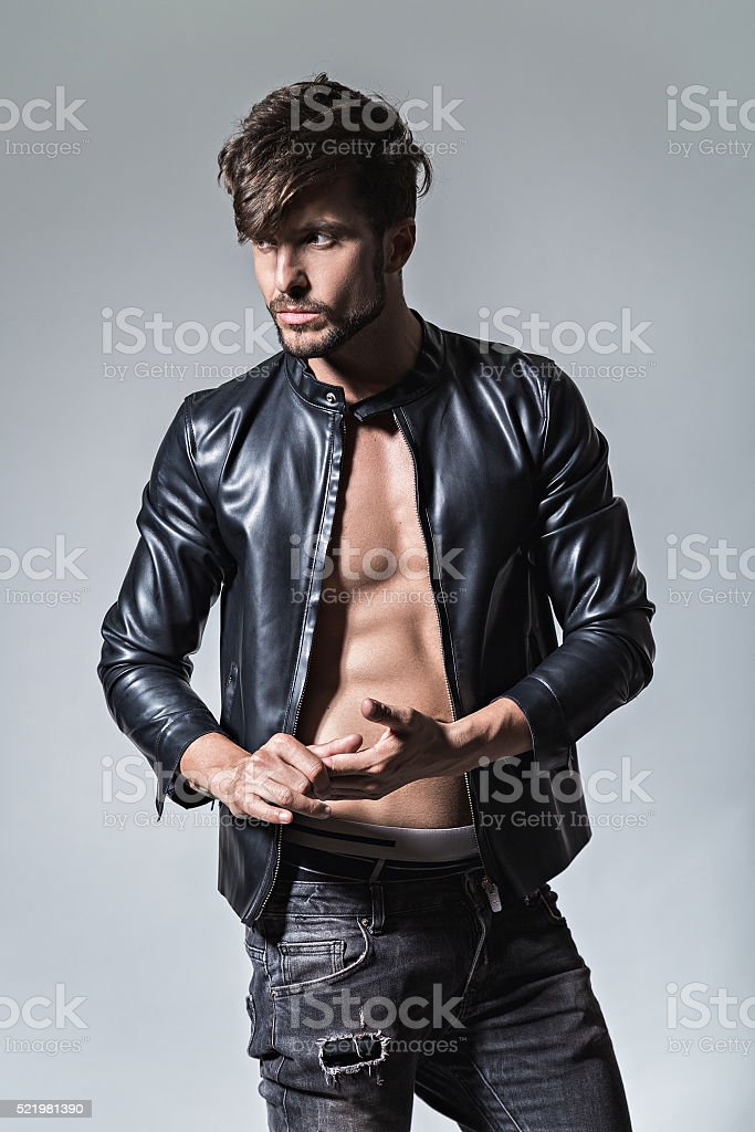 Man with attitude in leather jacket and jeans stock photo