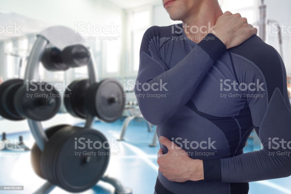 Man with back and neck pain in gym. Sports exercising injury stock photo