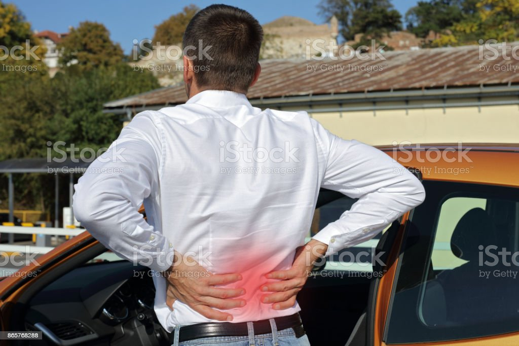Man with back pain after long car drive. Incorrect sitting posture problems ,Muscle spasm, rheumatism. Pain relief, ,chiropractic concept. stock photo