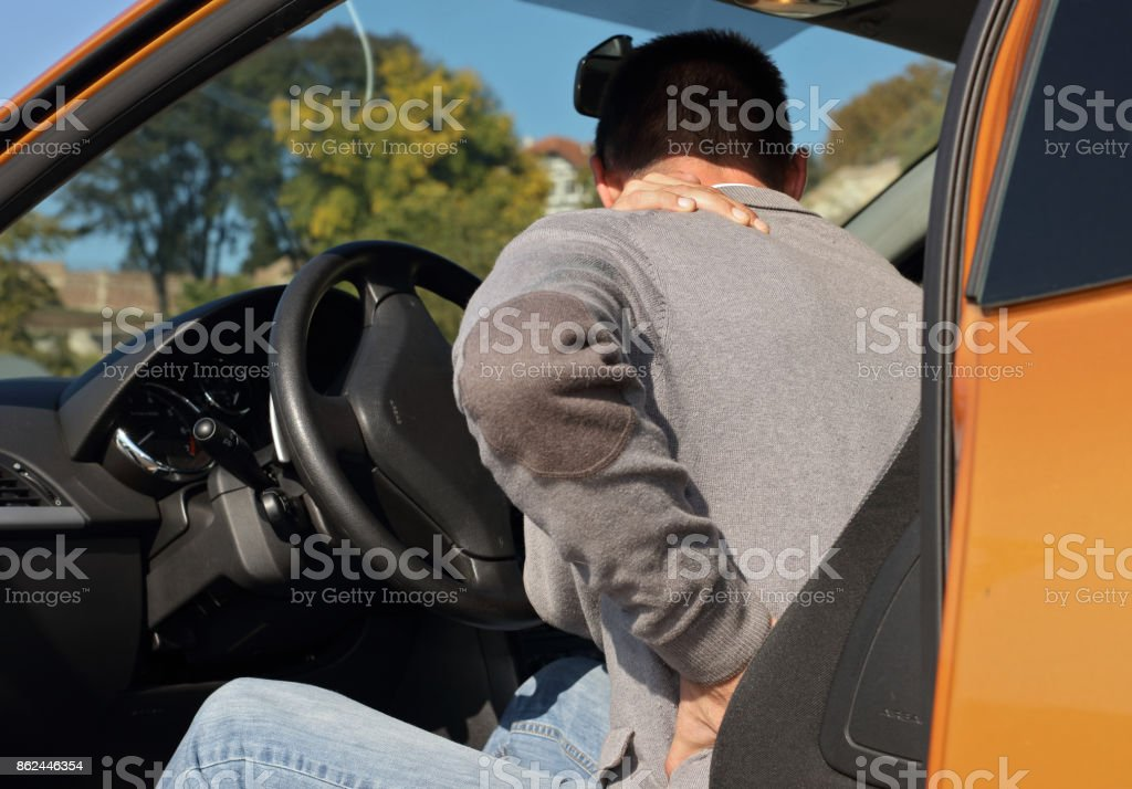 Man with back pain after long car drive. Pain relief and health care concept. stock photo
