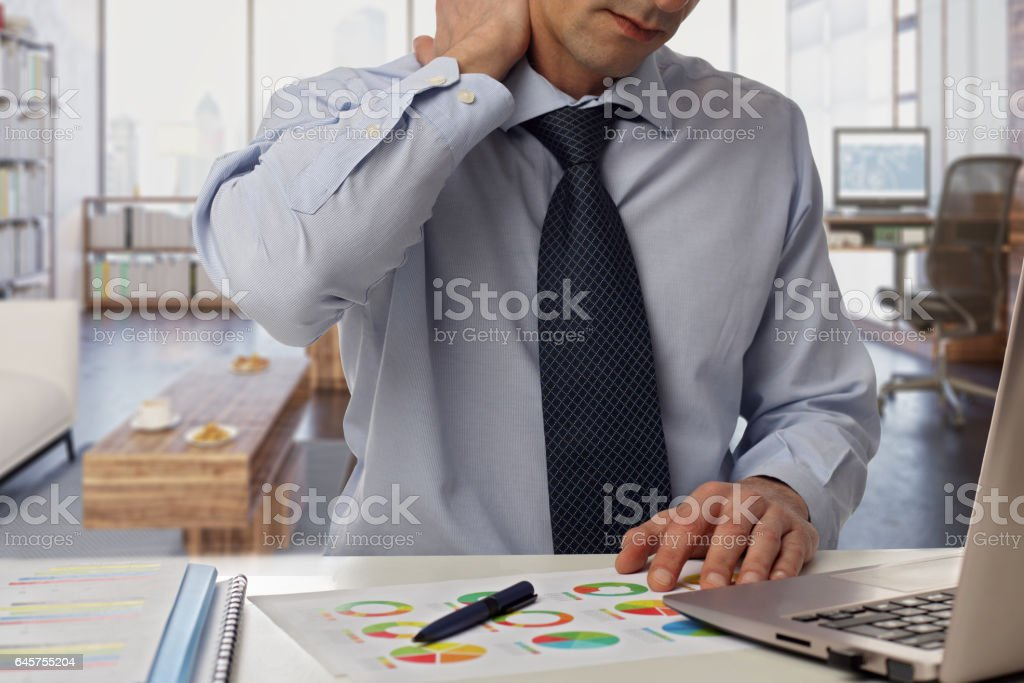 Man with back pain. Business man rubbing his painful neck stock photo