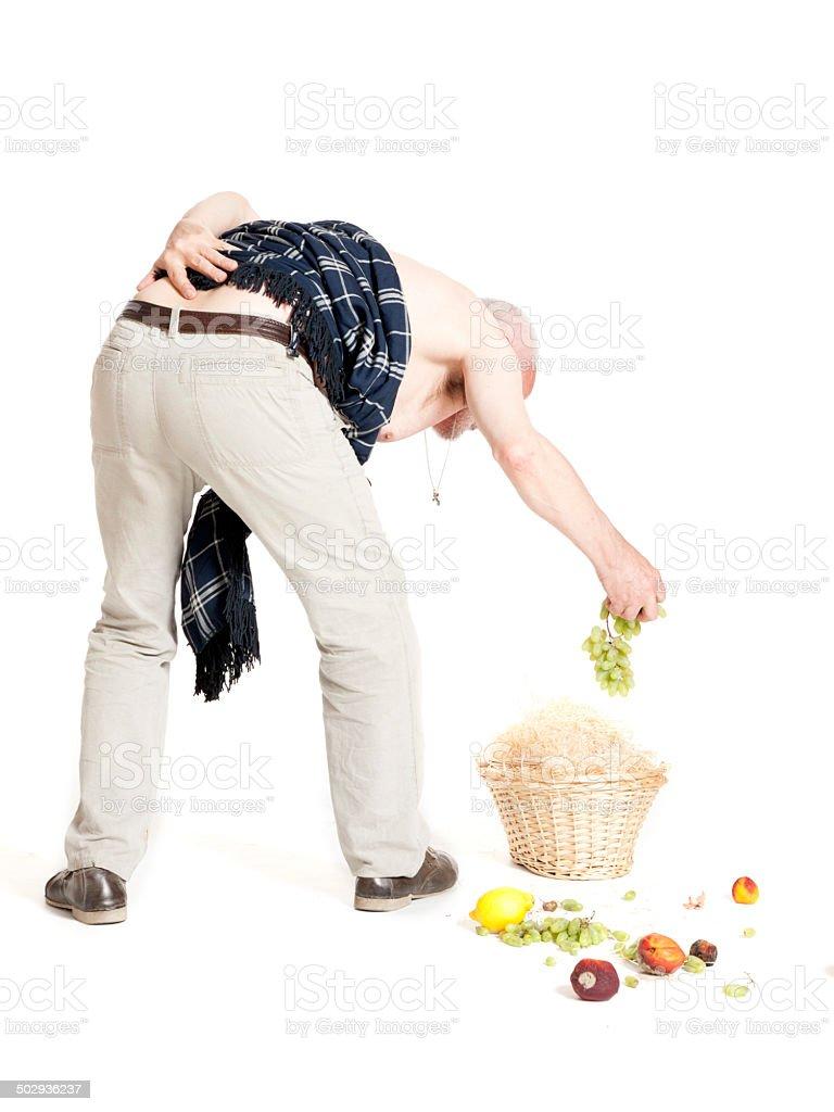 Man with back pain dropped fruit basket stock photo