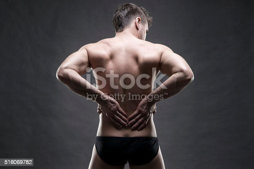 578088054istockphoto Man with backache on gray background 516069782
