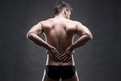 537234318 istock photo Man with backache on gray background 516069782