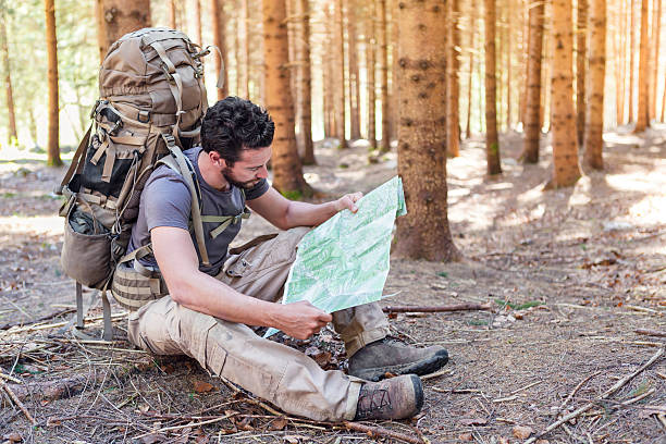 Man with Backpack and map searching directions stock photo