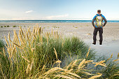 Hiker Man with Backpack hiking amazing in windy coastal sand dune marram grass towards beach of North Sea. Beach access dunes in soft evening sunset light. Skagen Nordstrand, Denmark where Baltic Sea and North Sea are colliding. Skagerrak, Kattegat.