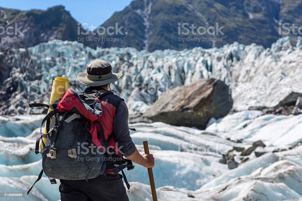Man with Backpack Hiking on Fox Glacier, New Zealand stock photo