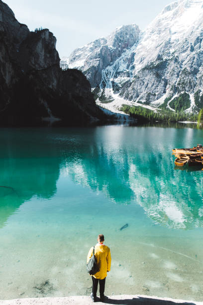 Man with backpack in raincoat looking at Lago Di Braies during summer sunrise stock photo