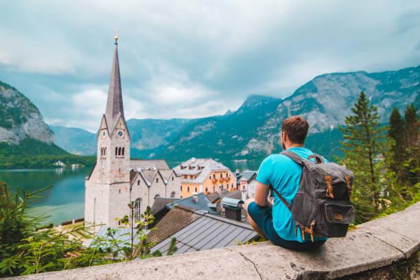 man with backpack sitting and enjoying the vie of hallstatt austria stock photo