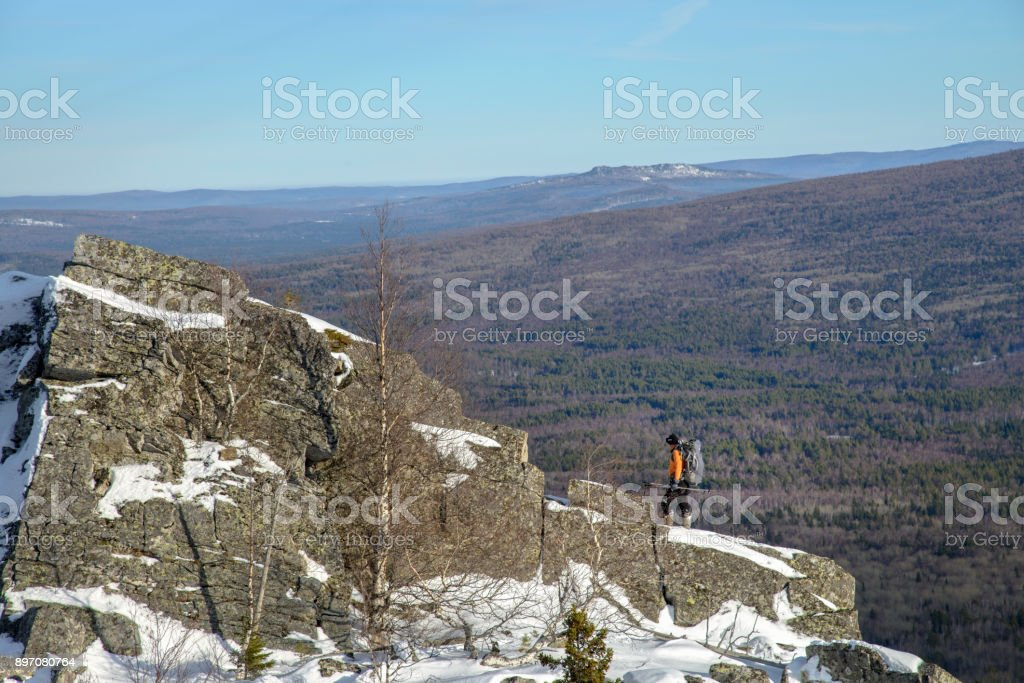 Man with backpack trekking in mountains at winter. Hiker at the top the rock covered with snow. stock photo