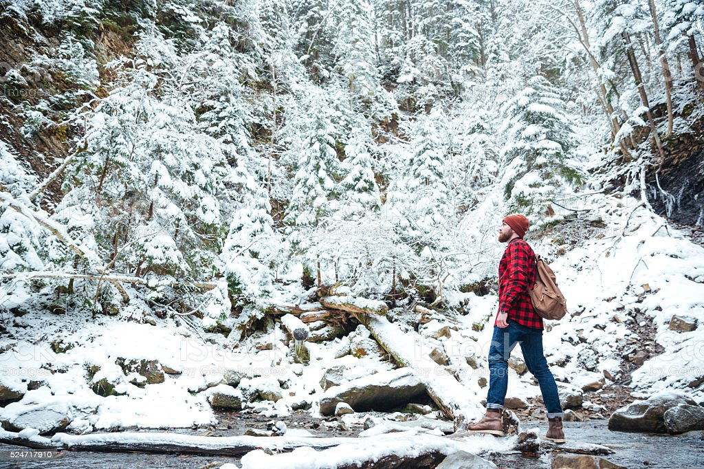 Man with backpack walking near the river in winter forest stock photo