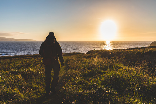 Man with backpack walking toward the sea at sunset