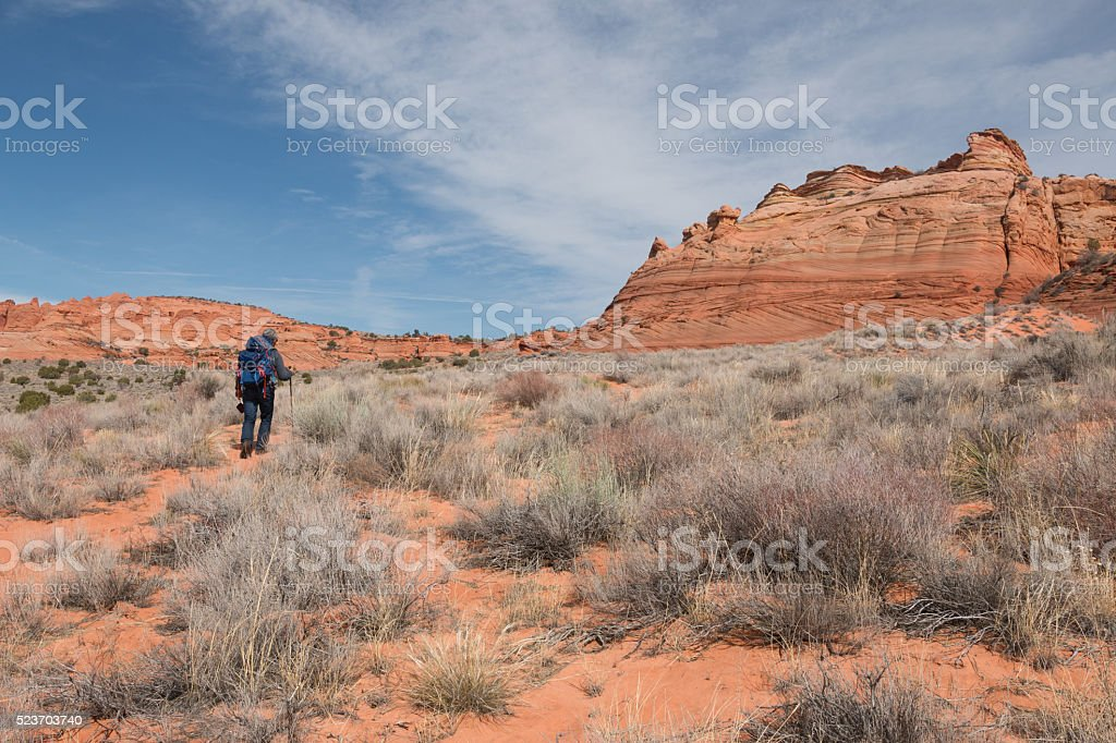 Man with backpack  walks towards sandstone buttes stock photo