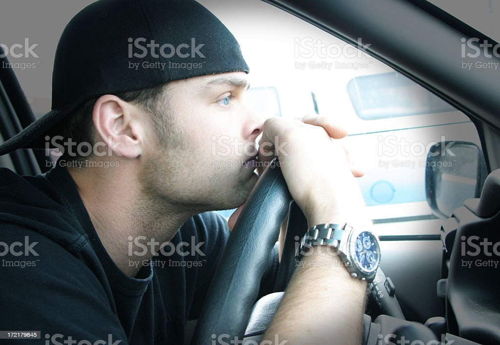 Man with backward hat and face on steering wheel of a car royalty-free stock photo