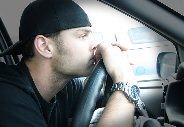 Man with backward hat and face on steering wheel of a car stock photo