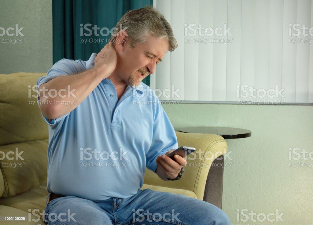 Mann mit schlimmen Fall von Tablet Hals-Syndrom eine chronische Schmerzen Zustand von Tech sucht mit Smartphone zu viel – Foto