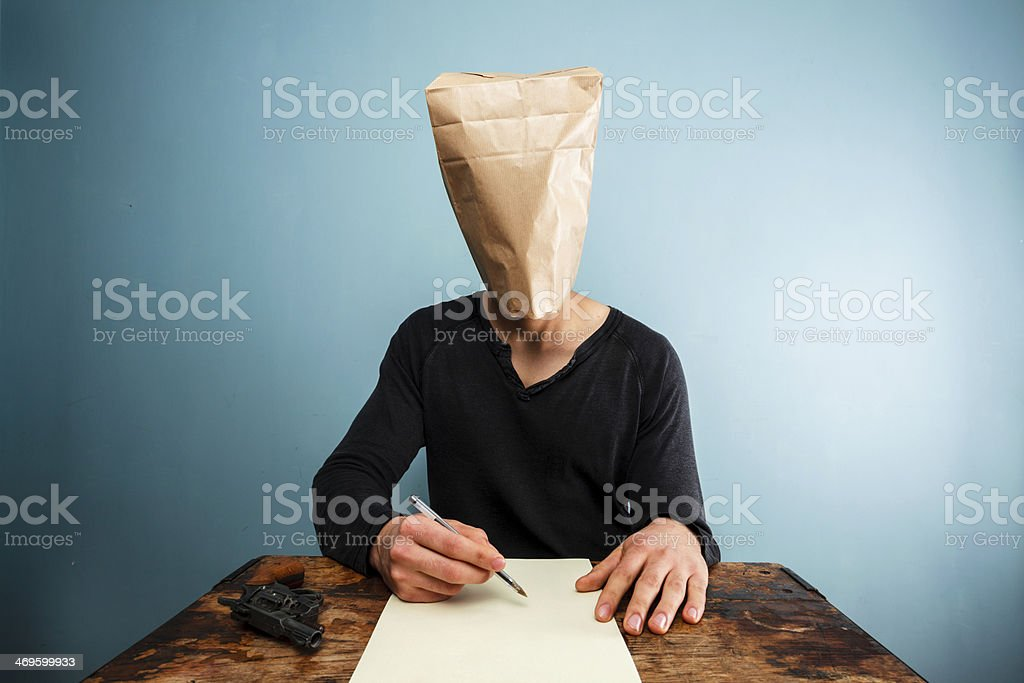 Man with bag over head writing suicide note stock photo