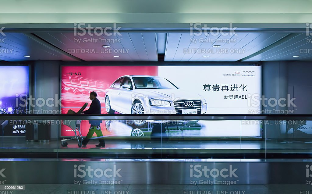 Man with baggage trolley passes Audi billboard, Beijing Capital Airport stock photo