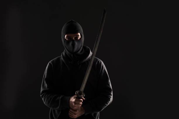 hombre con pasamontañas y katana espada sobre fondo negro - ninja fotografías e imágenes de stock