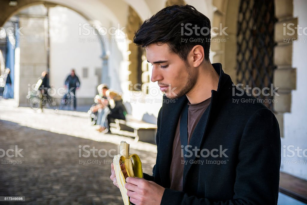 Man with banana standing on street in Lausanne while looking stock photo