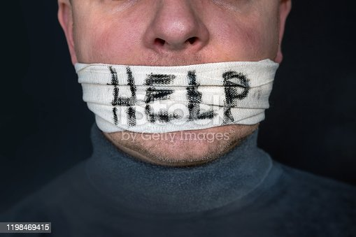 1091817198 istock photo Man with bandage over his mouth and the word help in English 1198469415