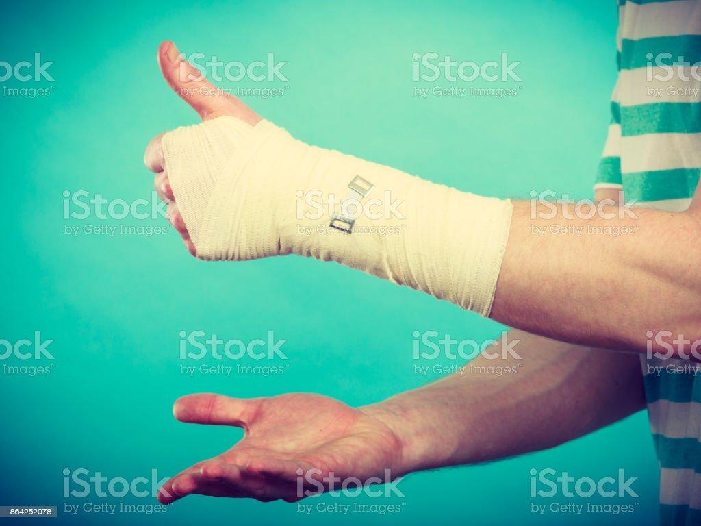Man with bandaged hand showing thumb up. royalty-free stock photo