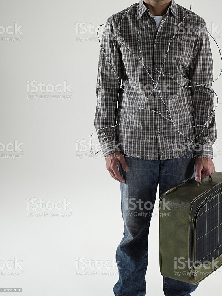 Man with barbed wire and suitcase royalty-free stock photo