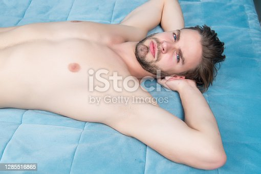 Man with bare torso, chest lie on blue bed cover.