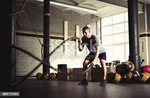istock Man with battle ropes in gym. 888732652