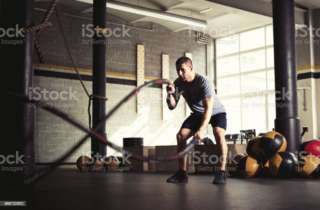 Man with battle ropes in gym. stock photo