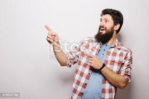 istock Man with beard demonstrate  invisible product advertising  pointed with hands 515237762