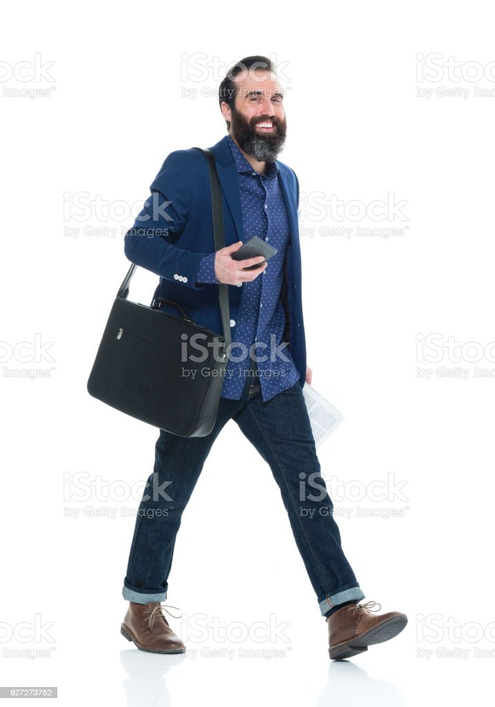 Man with beard holding bag and phone and walking stock photo