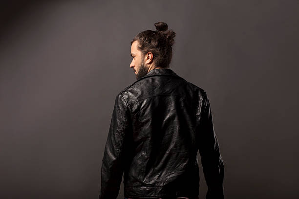 man with beard in a black leather jacket back view of man with beard and bun in black leather jacket man bun stock pictures, royalty-free photos & images