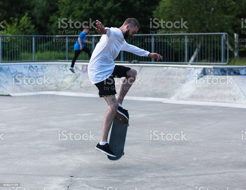 Man with beard mid skateboard trick stock photo