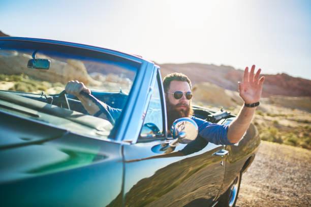 man with beard sitting in vintage car waving - homme faire coucou voiture photos et images de collection