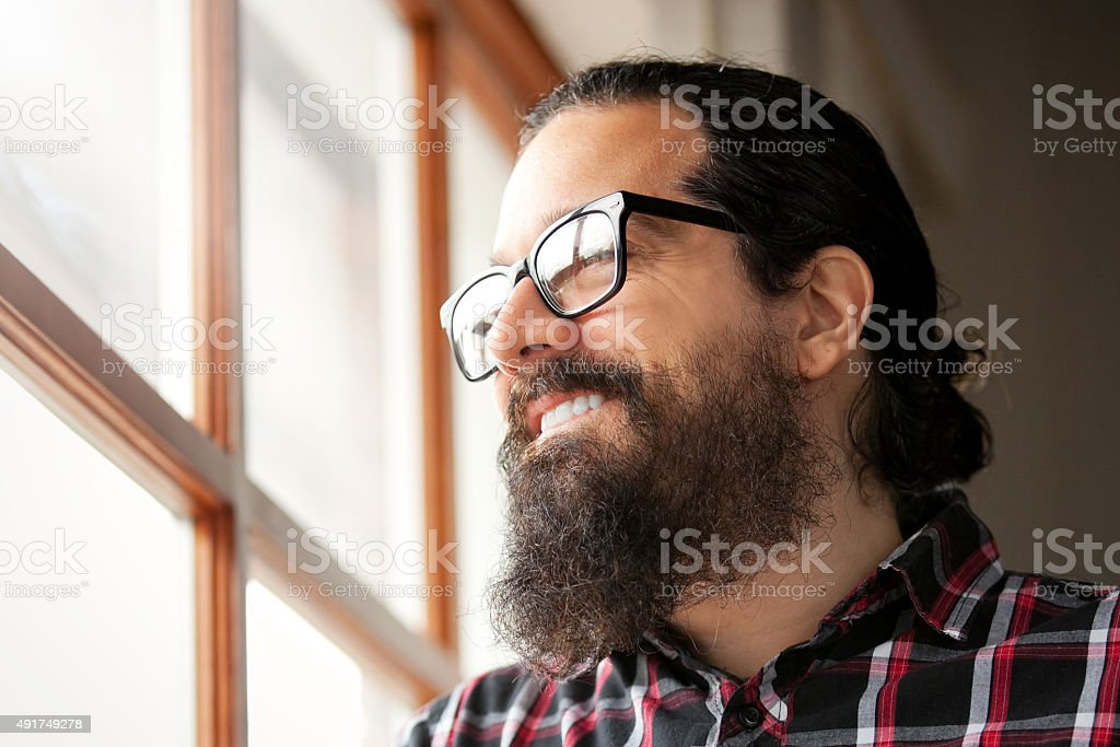 Man WIth Beard Smiling As He Looks Through Window. stock photo