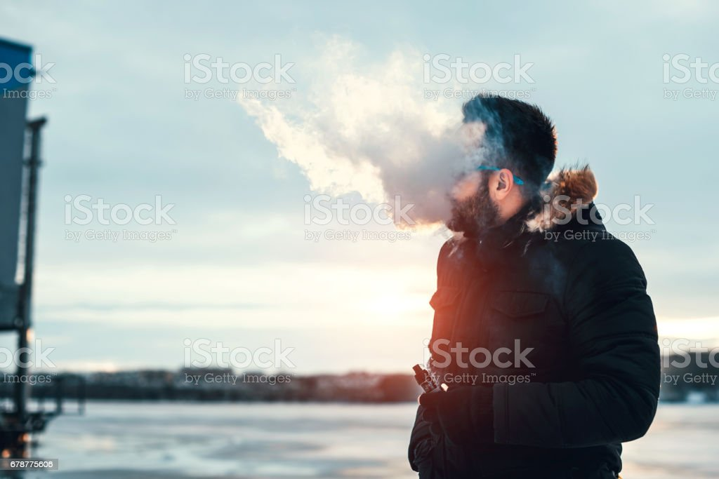 Man with beard smoke electronic cigarette outdoor royalty-free stock photo