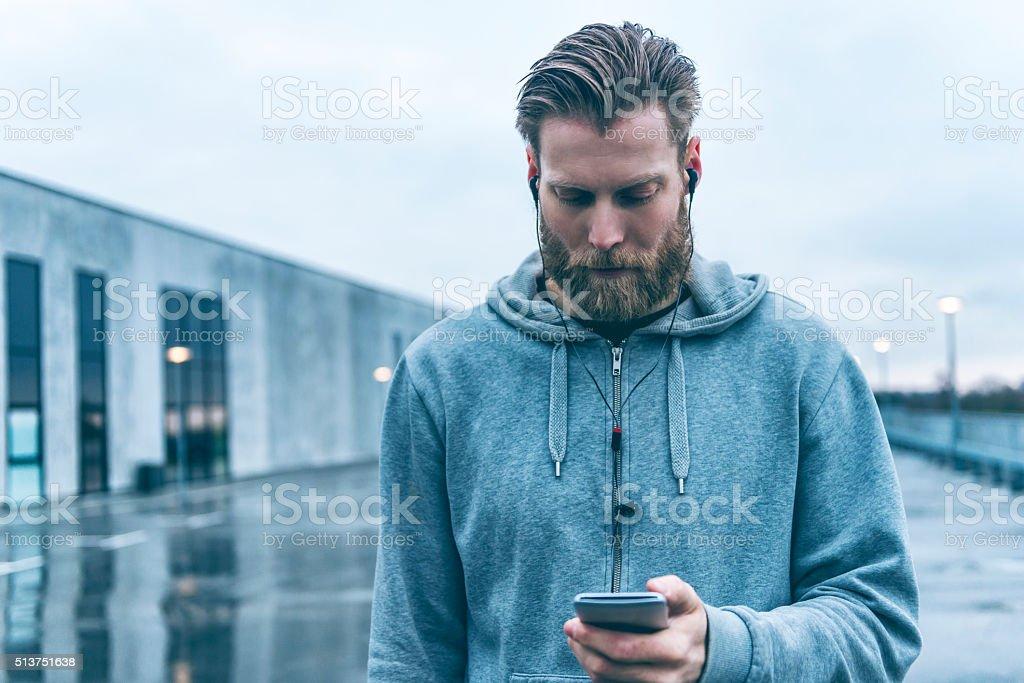 Man with beard uses smart phone outside stock photo