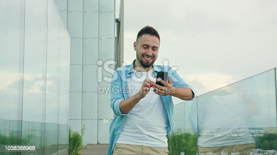 istock Man with Beard Using a Phone in Town 1038388968
