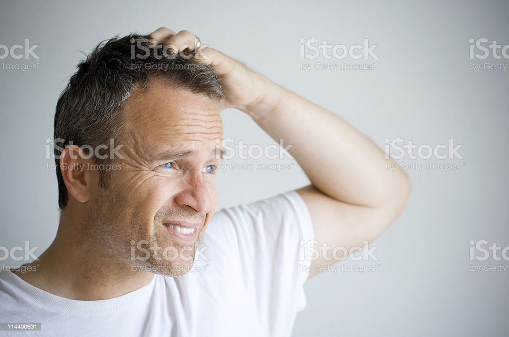 Man with bedhead trying to cover his hair with hand stock photo
