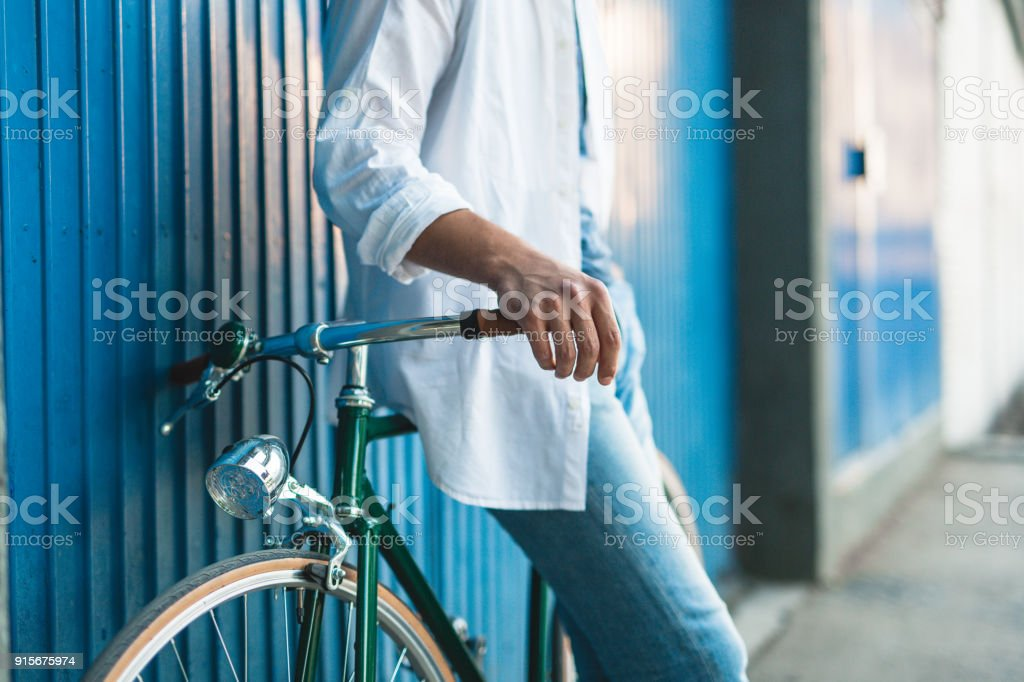 Mann mit Fahrrad stützte sich auf blaue Garagentor – Foto