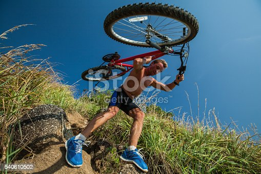 Half-naked sportsman carrying a bicycle