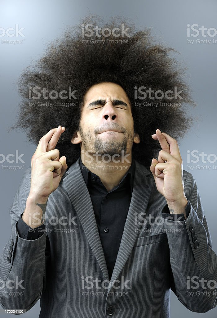 man with big hair keeping fingers crossed stock photo