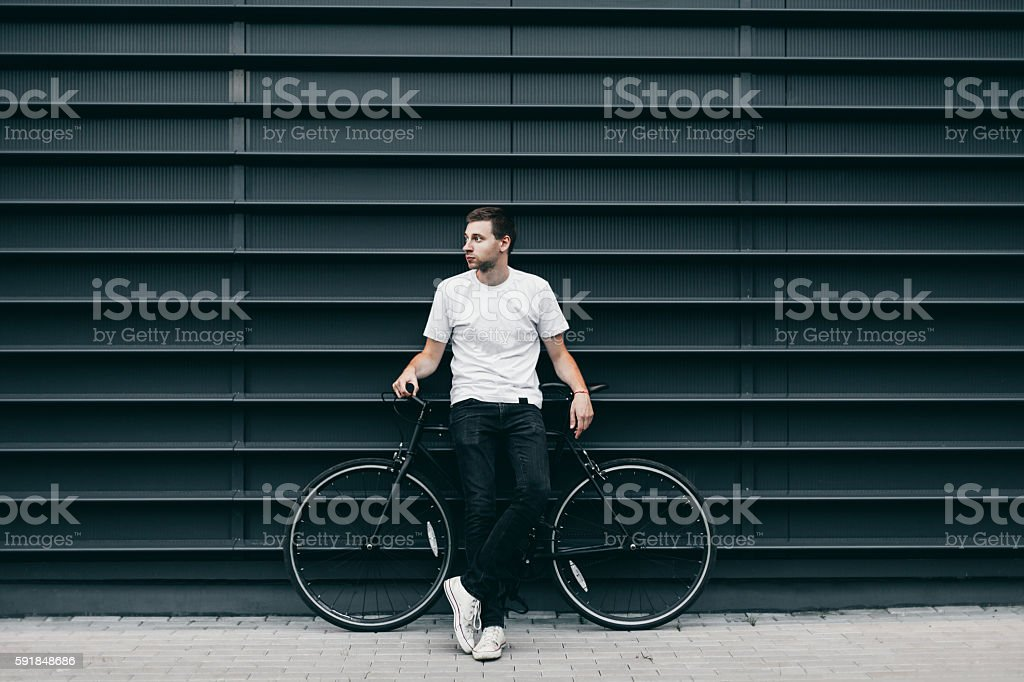 Man with bike in city - Photo