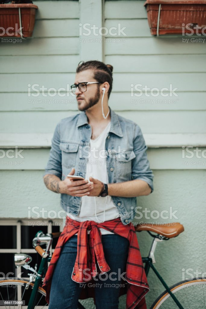 Man with bike leaned on the wall is listening to a podcast royalty-free stock photo