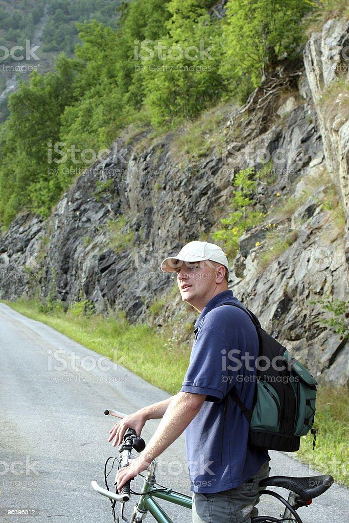 Man with bike on mountain trip stock photo