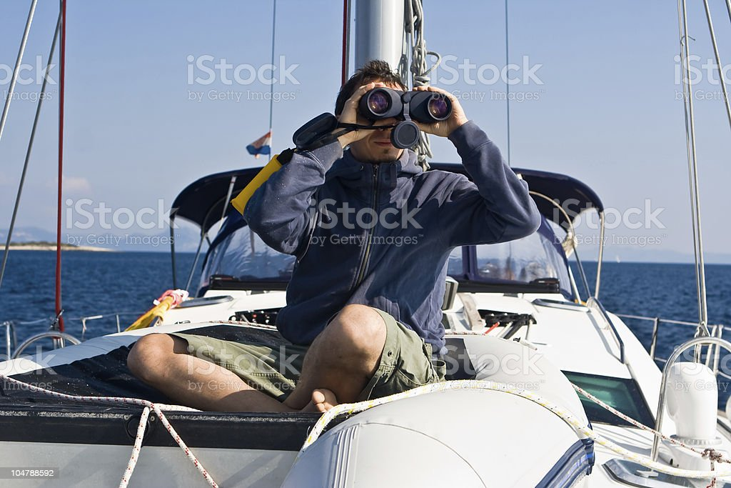 Man with binocular on the yacht royalty-free stock photo